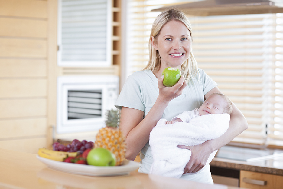 Smiling woman with an apple and her baby on her arms