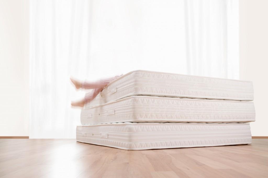 Girl playing on three mattress on wooden floor.