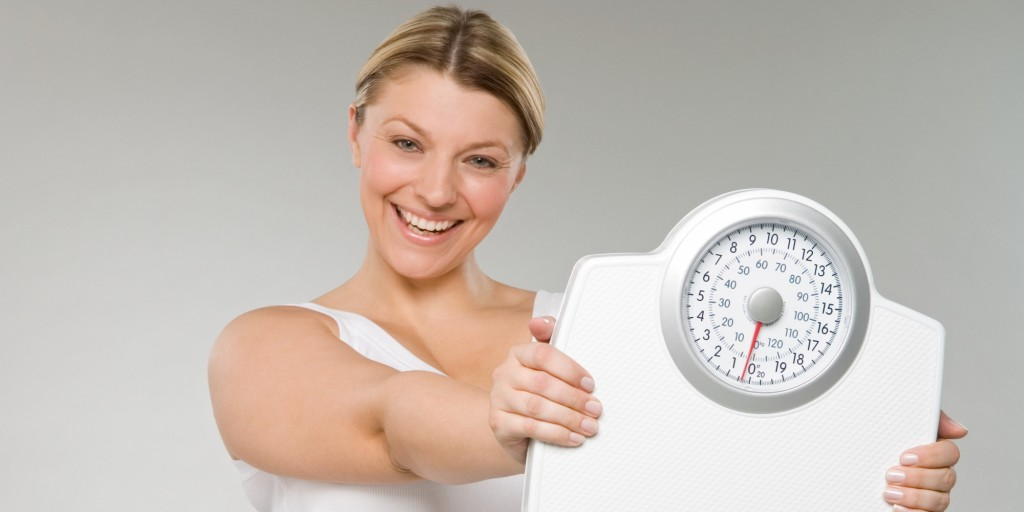 A woman holding weight scales