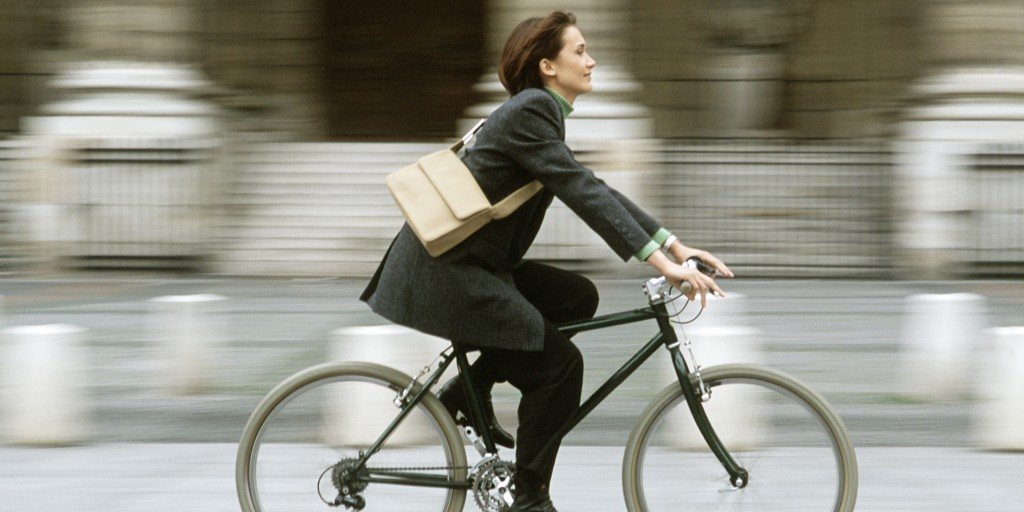 Well dressed woman riding bicycle down city sidewalk